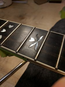 broken inlay on a banjo neck that will be restored